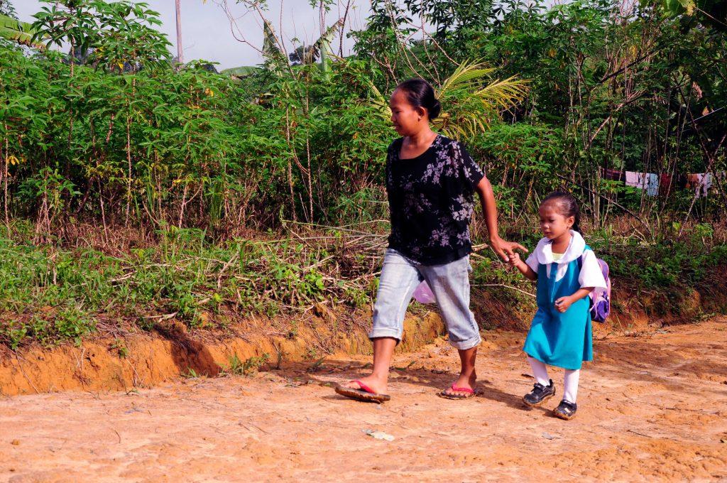 Seorang ibu sedang mengantarkan anaknya ke Sekolah